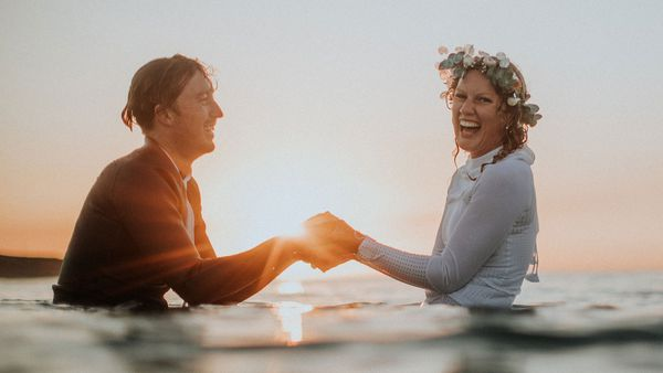 Australian bride and groom surf together before beach wedding