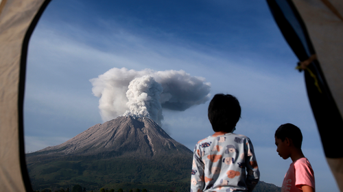Indonesian youths are seen from the opening of a tent as they watch Mount Sinabung erupting in Karo, North Sumatra, Indonesia, Thursday, March 11, 2021. (AP Photo/Binsar Bakkara)