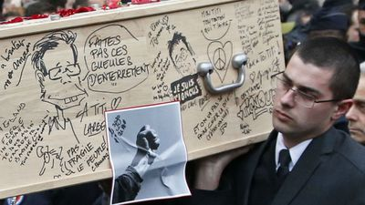 Tignous' coffin is carried from the Town Hall building, its exterior covered in cartoons remembering the often controversial cartoonist. (AFP)