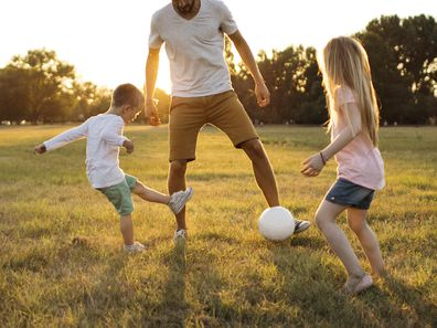Kids and father playing soccer on a beautiful summer afternoon outdoors