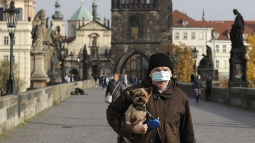 A man wearing a face mask carries his dog across the medieval Charles Bridge in Prague, Czech Republic, Wednesday, Oct. 21, 2020