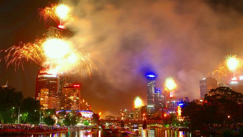 Crowds pack the banks of the Yarra as fireworks light up the sky above Melbourne. (AAP)
