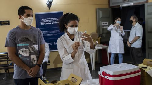 A health worker prepares a shot of the AstraZeneca vaccine for COVID-19 during a vaccination campaign for people over age 35 in Rio de Janeiro
