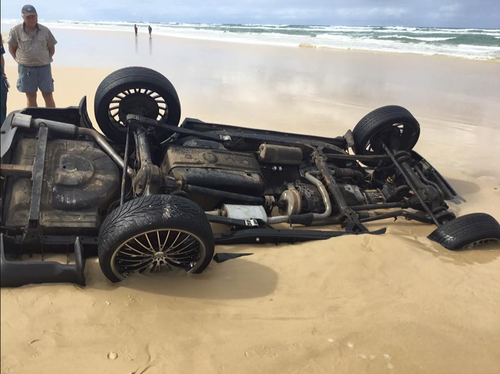 By the time the recovery team were able to access the Range Rover, only its tires and underside were visible about the sand. (Queensland Ambulance Service)