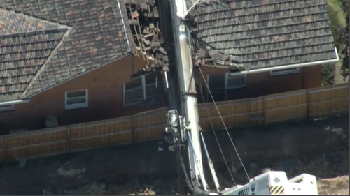 The fallen drill rig has caused significant damage to the roof of the home.