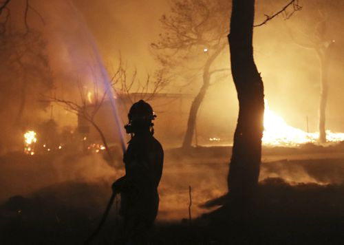 A firefighter sprays water on the fire in the town of Mati. Picture: AP