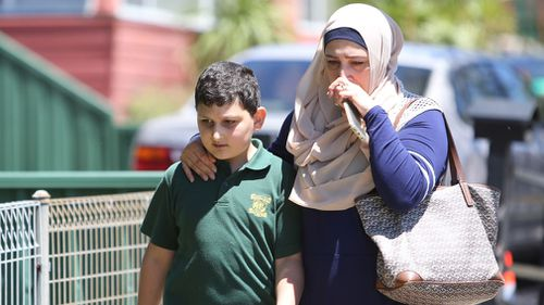 A distressed parent leaves the school with their child. (AAP)