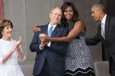 First Lady Michelle Obama hugs former President George W Bush at the opening of the National Museum of African American History and Culture, Washington DC, September 24, 2016.