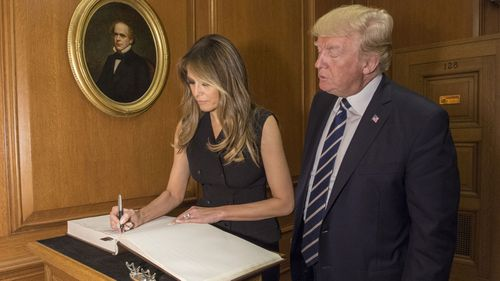 In this image provided by the Supreme Court, President Donald Trump watches as first lady Melania Trump signs the Supreme Court guest book, Thursday, June 15, 2017, at the Supreme Court in Washington.