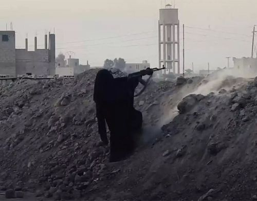 A scene from a recent Islamic State propaganda video appearing to show a black-robed woman fighting in Syria.