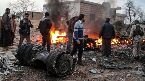 People walk amidst the rubble of the Russian Sukhoi Su-25 fighter jet. (AAP)