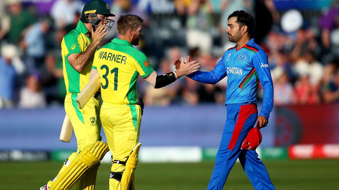 David Warner and Glenn Maxwell of Australia shake hands with Rashid Khan of Afghanistan.