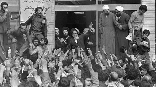 Ayatollah Ruhollah Khomeini, center, waves to followers as he appears on the balcony of his headquarters in Tehran in 1979.