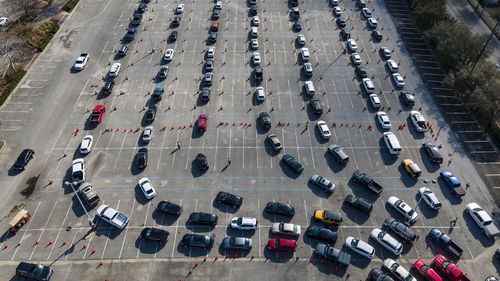 Cars line up in a parking lot at NRG Park as people wait to receive a COVID-19 vaccine at a federally supported supersite at the Harris County facility, Wednesday, Feb. 24, 2021, in Houston