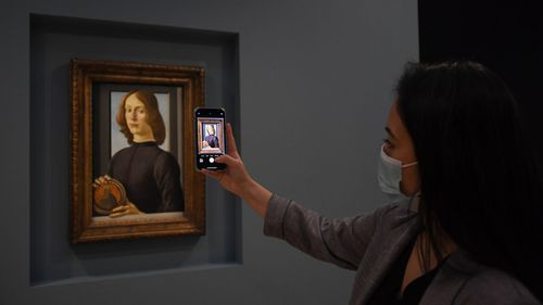 A member of the staff takes a phone picture of the painting 'Young Man Holding a Roundel' by the Italian Renaissance painter Sandro Botticelli at Sotheby's, in London, Wednesday, Dec. 2, 2020