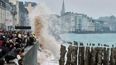 People watched the waves on the sea wall of the Port of Les Sables-d'Olonne, western France, during high tide.