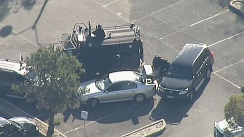 Specialist police surround the vehicle. (9NEWS)