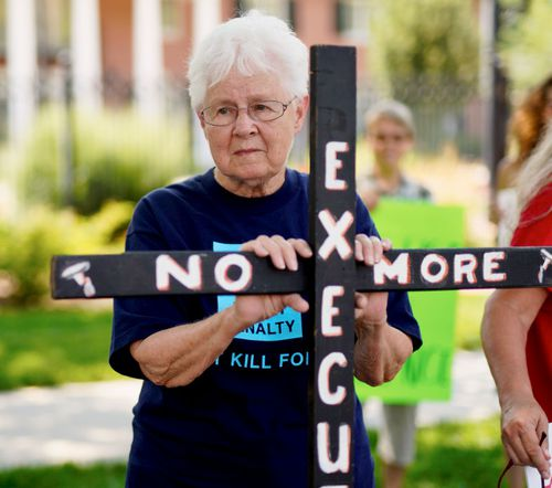 """Campaigner Marylyn Felion holds on to a cross reading """"No More Executions"""" as she pickets with others against the death penalty, in front of the governor's mansion in Lincoln, Nebraska."""