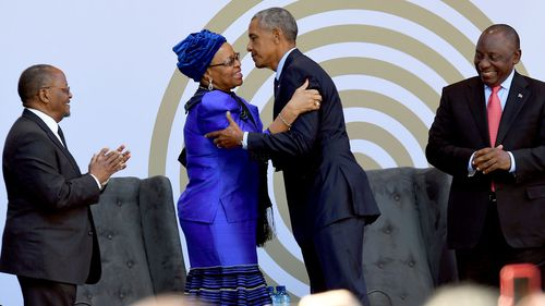 Former US President Barack Obama greets Nelson Mandela's widow Graca Machel, along with South African President Cyril Ramaphosa (far right) and Prof. Njabulo Ndebele (far left) in Johannesburg. (AAP)