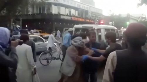 In this image taken from video, people tend to a wounded person near the site of a deadly explosion outside the airport in Kabul, Afghanistan.