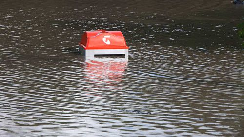 A phone booth in the suburb of Fairfield is inundated by the floodwaters.
