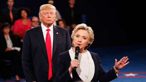 Democratic presidential nominee former Secretary of State Hillary Clinton speaks as Republican presidential nominee Donald Trump listens during the town hall debate at Washington University on October 9, 2016 in St Louis, Missouri. (Getty)