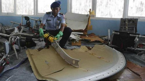 An Indonesian air force soldier holds pieces from AirAsia Flight 8501 at Disaster Victim Identification room at Pangkalan Bun. (AP)