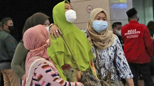 Relatives of passengers arrive at a crisis centre set up following a report that a Sriwijaya Air passenger jet has lost contact with air traffic controllers shortly after take off, at Soekarno-Hatta International Airport in Tangerang, Indonesia,Saturday, Jan. 9, 2021