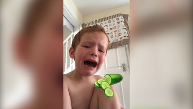 This little boy really loves eating cucumbers