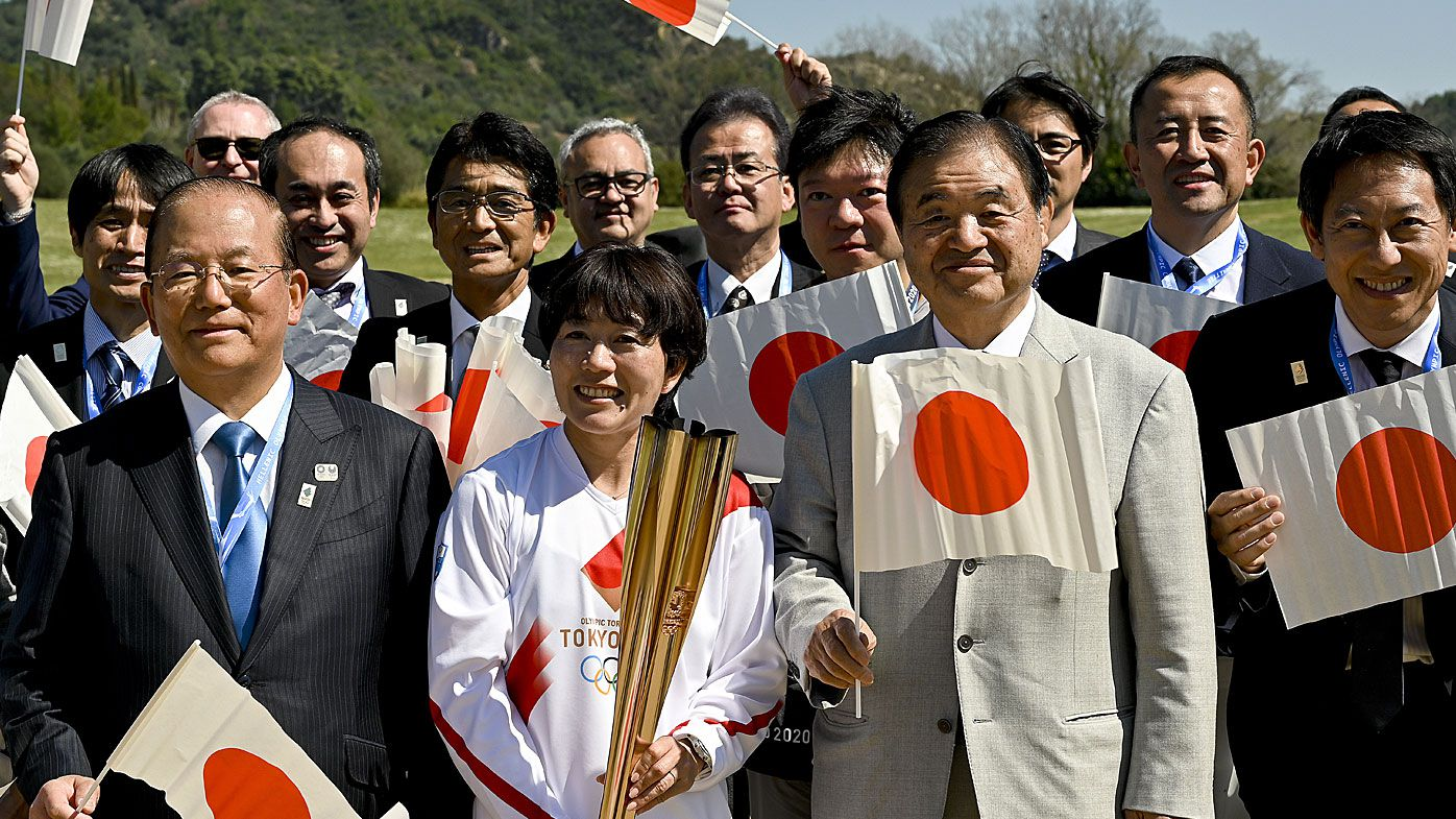 Japanese former marathon runner Noguchi Mizuki and president of the Tokyo 2020 Organising Committee Toshiaki Endo pose for a picture following the Olympic flame lighting ceremony