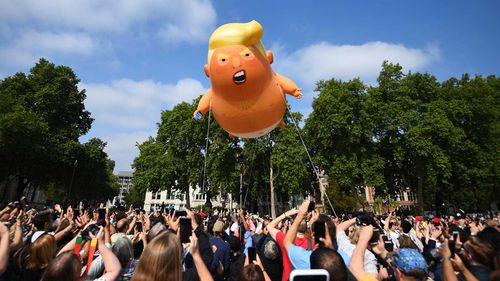 The Trump balloon rising above Parliament Square. (AAP)