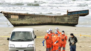 Japanese officials gather on Monday near a boat washed ashore in Oga, Akita Prefecture. (AAP)