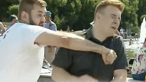 A still image shows reporter Nikita Razvozzhayev  being struck during a live TV broadcast. (Supplied)