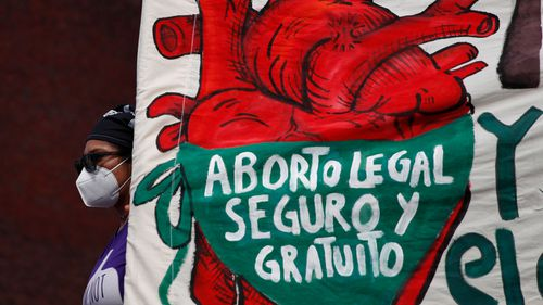 """A woman holds a banner reading, in Spanish, """"Legal, safe, and free abortion, legalise and decriminalise abortion now, for the independence and autonomy of our bodies,"""" at a protest last September in Mexico City."""