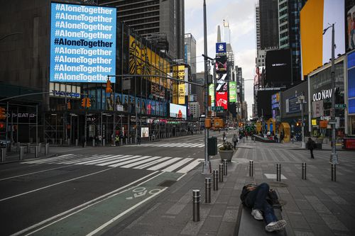 A billboard displaying hashtags concerning COVID-19 hangs over a sparsely populated Times Square, Friday, March 20, 2020, in New York. New York Gov. Andrew Cuomo is ordering all workers in non-essential businesses to stay home and banning gatherings statewide. Only essential businesses can have workers commuting to the job or on the job, Cuomo said of an executive order he will sign Friday. Nonessential gatherings of individuals of any size or for any reason are canceled or postponed. (AP Photo/