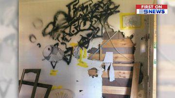 Holes and graffiti on a wall.