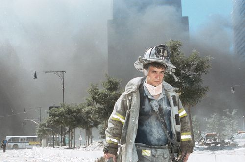 Covered in dust and with smoke in the distance, an unidentified New York City firefighter walks away from Ground Zero after the collapse of the Twin Towers on September 11, 2001.