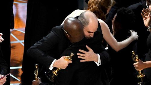 The producer embraces Moonlight director Barry Jenkins. (Getty)