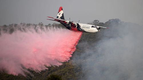 The NSW Rural Fire Service Large Air Tanker (LAT) drops fire retardant on the Morton Fire burning in bushland close to homes at Penrose in the NSW Southern Highlands, 165km south of Sydney, Friday, January 10, 2020