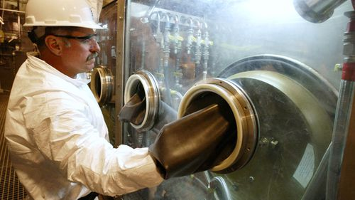David Ardoin, an operator for Parsons Infrastructure and Technology Group Inc. of Pasadena, Calif. demonstrates the enclosed CHATS system where the nerve agent VX is drained from the ton containers to begin the process of chemically neutralizing the stockpile. (AP)