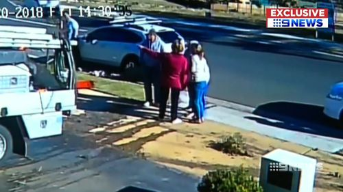 Shocked neighbours gather while the driver makes his getaway in a woman's car. Picture: 9NEWS
