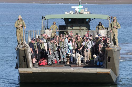 Mallacoota evacuees are brought to shore on landing crafts in Hastings.