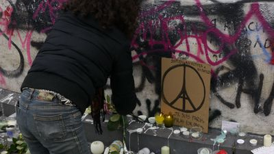 A woman lights a candle near a Parisian peace sign at Place de la Republique. (Jack Hawke, 9News.com.au)