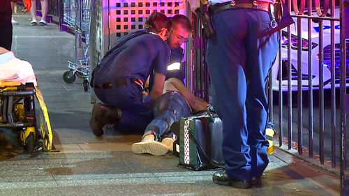 Paramedics treat an injured man outside Burwood Railway Station.