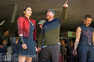 Director Joss Whedon is back at the helm, giving Elizabeth and Jeremy pointers as they film a scene. What we wouldn't give to be one of those extras in the background...
