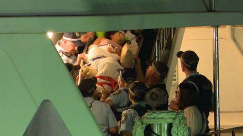 The 21-year-old party host was stretchered from the vessel. (9NEWS)
