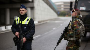 A Belgian police officer and a soldier stand guard at Brussels airport.