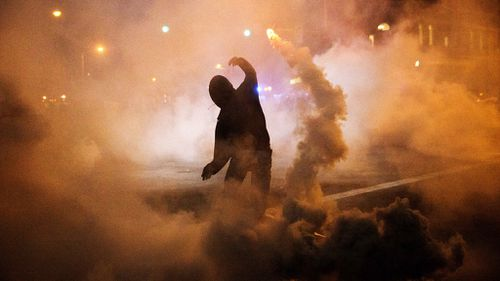 A protester hurls a smoke bomb canister back towards police. (AAP)