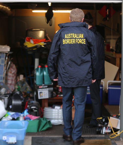 An Australian Border Force agent walks into a garage at the Bathurst address.