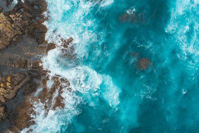 Stock image of ocean current, waves crashing against rocks.